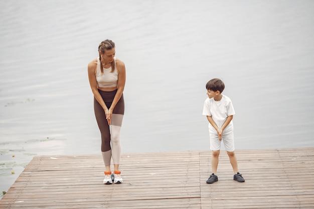息子と母親は夏の公園で運動をしています。水辺の家族。