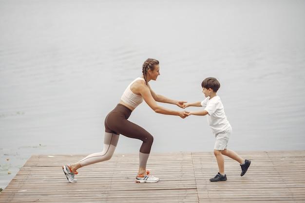 Сын и мама делают зарядку в летнем парке. семья у воды.