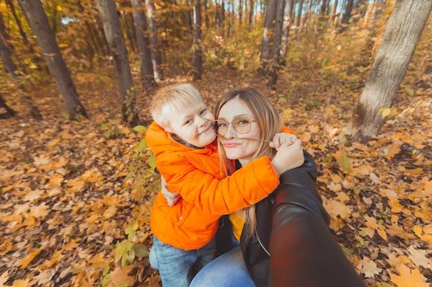 息子と母親が自分撮りをして、秋の公園のひとり親のレジャーと秋のシーズンを楽しんでいます