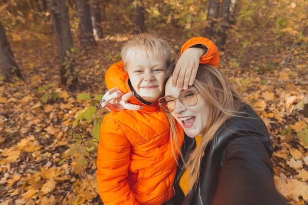 息子と母親が秋の公園でカメラで自分撮りをしています。ひとり親、レジャー、秋のシーズンのコンセプト。