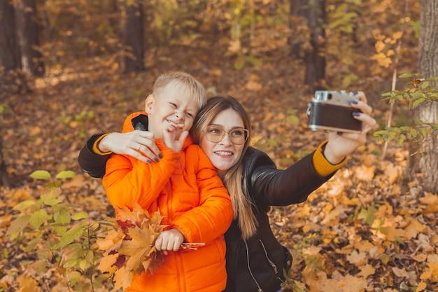 아들과 어머니는 가을 공원 미혼모 레저 및 가을 시즌에서 카메라로 셀카를 찍고 있습니다.