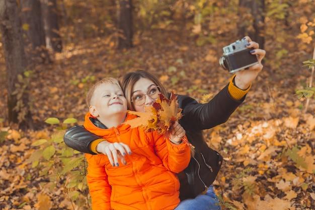 息子と母親が秋の公園のひとり親レジャーと秋のシーズンにカメラで自分撮りをしています