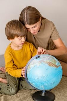 Сын и мать вместе смотрят на земной шар