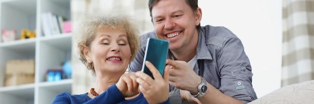 아들과 어머니는 웃고 전화 화면을 보고