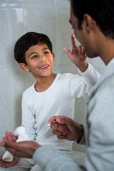 Son applying foam on fathers face