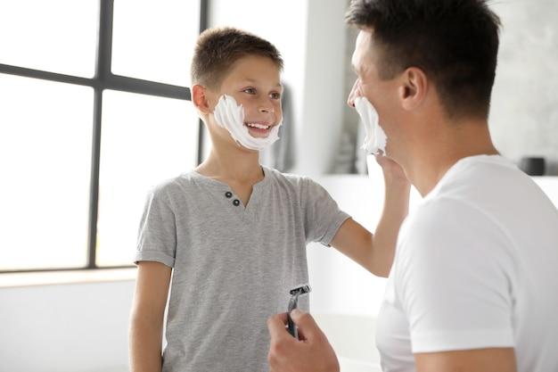 욕실에서 아버지의 얼굴에 면도 거품을 바르는 아들