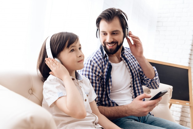 Son and dad listen to music together.