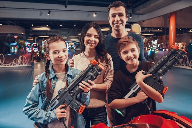 Son and daughter are shooting guns in arcade.