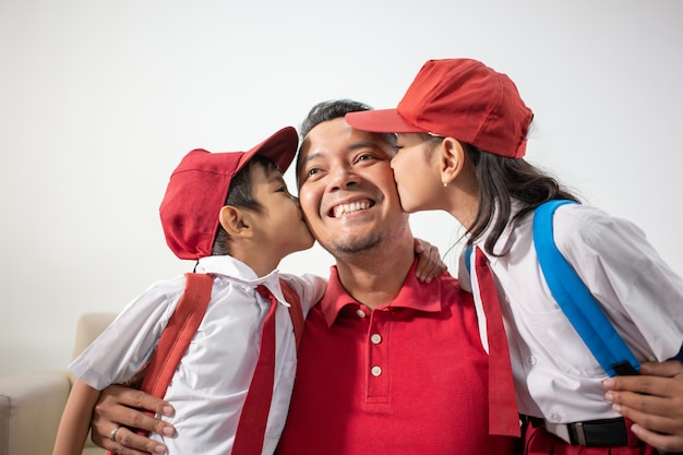 Son and daughter kiss father on cheek Premium Photo