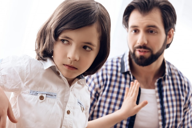 아들은 아빠를 용서하고 싶지 않으며 그를 멀리 밀어냅니다. 프리미엄 사진