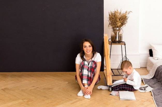 Son drawing on paper sitting on floor with happy mother