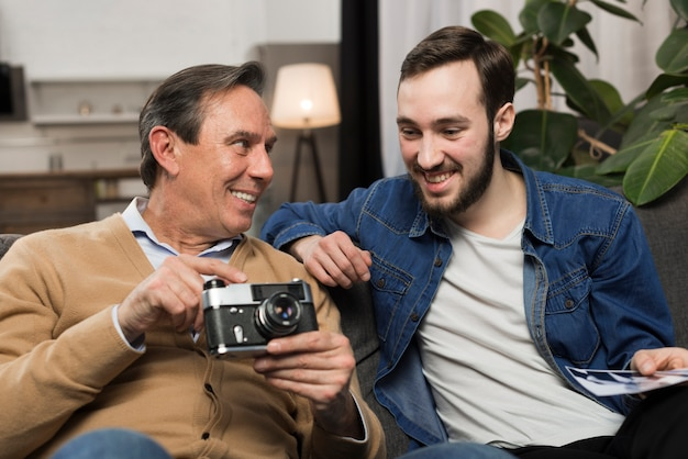 Son and father looking at photos in living room