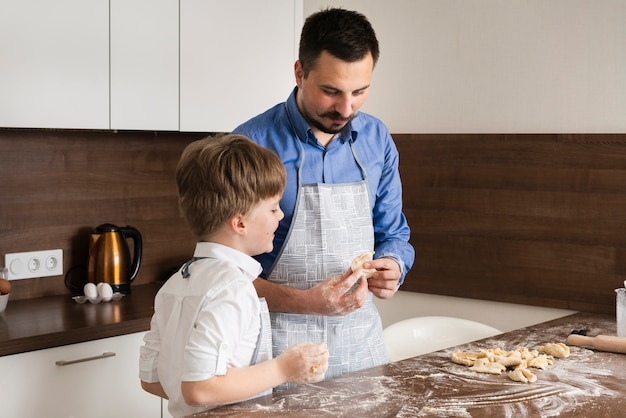 Son and father making dough together