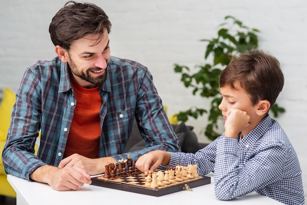Son and father playing chess