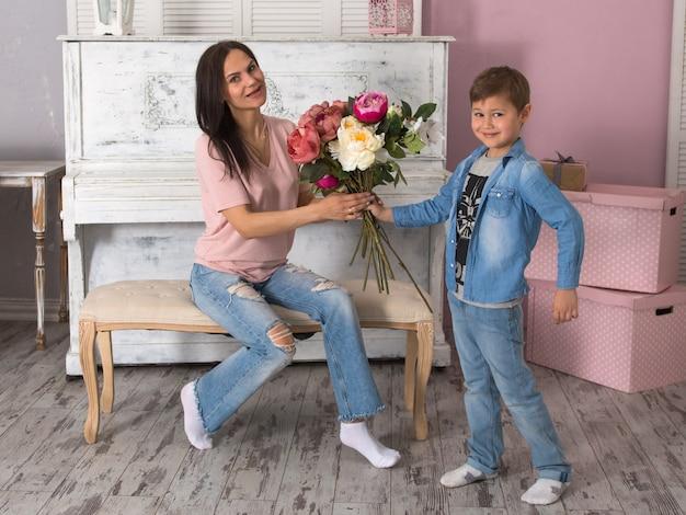 Son gives mom a bouquet of flowers, mothers day concept