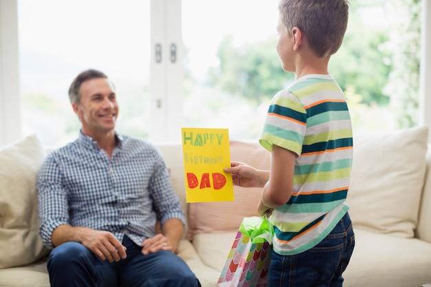 거실에서 아버지에게 생일 카드를주는 아들