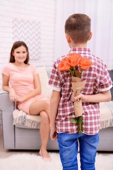 Сын прячет за спиной розы для матери