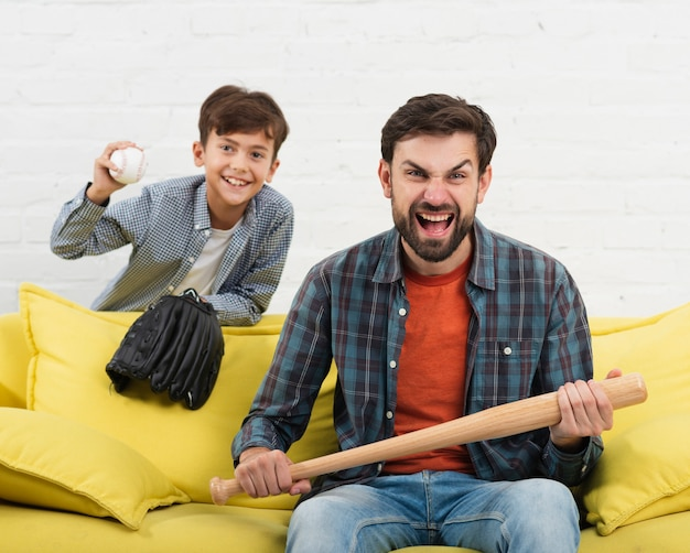 Son holding a ball and father a a baseball bat