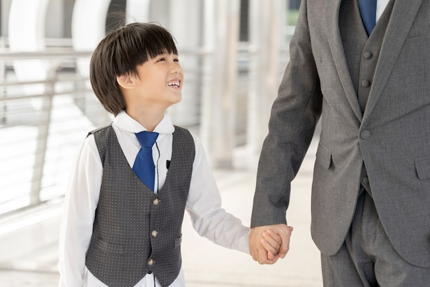 Son holding father's hand on business district urban