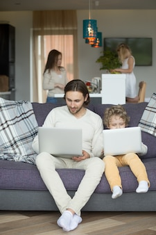 Son imitating father sitting on couch holding laptop at home