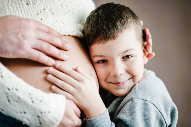 아들은 그의 아름다운 임신 어머니 배를 듣고 웃고