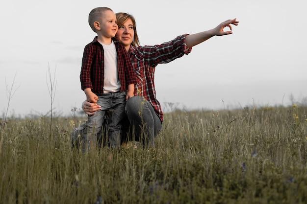 아들은 엄마의 팔에 앉아 있습니다. 행복한 가족의 야외 레크리에이션