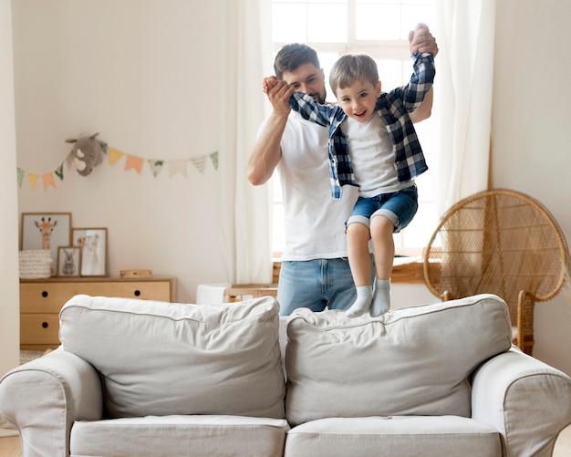 Сын прыгает на диване и удерживается отцом