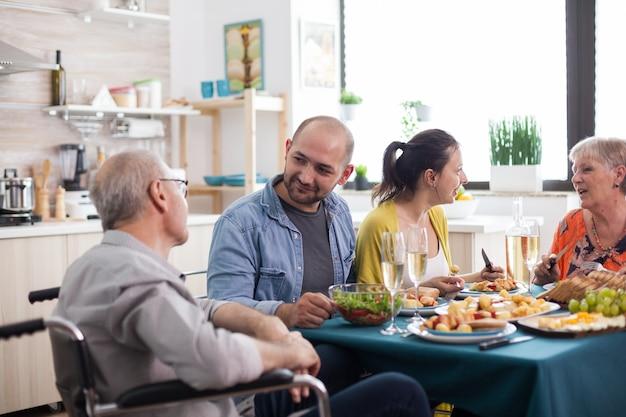 건강한 음식으로 가족 점심을 먹는 동안 휠체어에 앉은 장애인 노인 아버지를 바라보는 아들. 행복한 성숙한 부모.