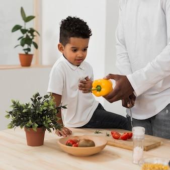 夕食を作っている父親を見ている息子