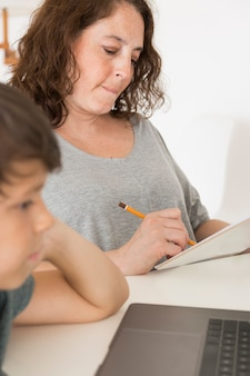 Son looking on laptop next to mom