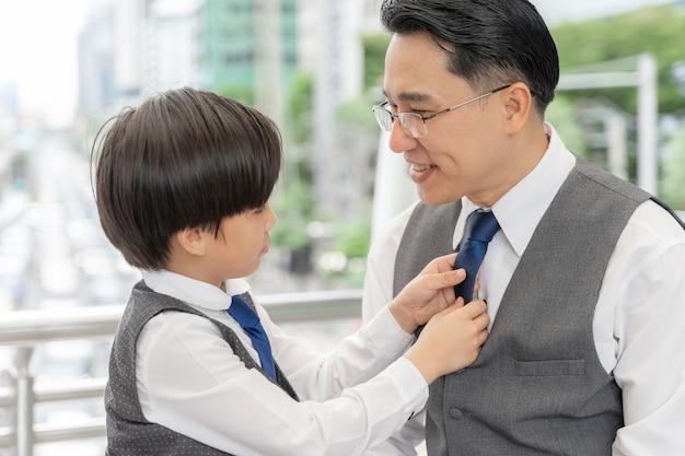 아들은 비즈니스 지구 도시에서 그의 아버지를 위해 옷깃을 만들었습니다.
