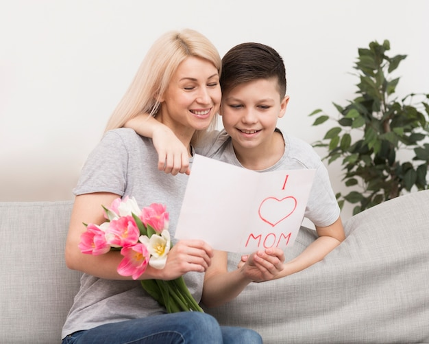 Son and mother on couch reading card