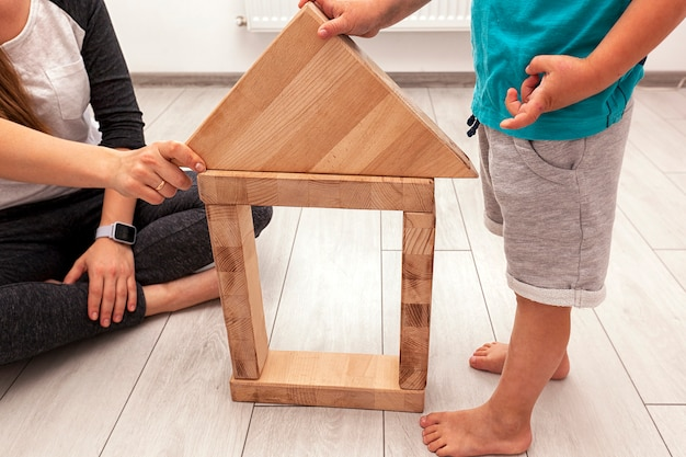 Son and mother is playing in room and build house from wooden blocks