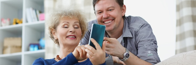 Son and mother smiling and looking at phone screen