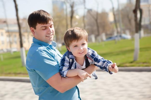 Сын на отцов в парке весело вместе