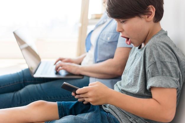 ママの横にあるスマートフォンで遊ぶ息子