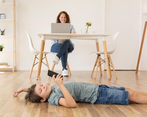 Сын играет на смартфоне рядом с мамой