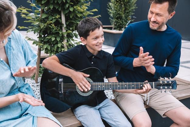 息子は、ギターを弾くことを学ぶことに成功したことで両親を喜ばせています。幸せな家族の概念。ライフスタイル。