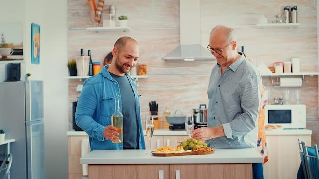 息子は父親のグラスにワインを注ぎ、新しいモダンなキッチンで歓声を上げ、笑顔で話します。居心地の良いダイニングルームに一緒に座っている拡大家族、健康的な夕食を準備している女性