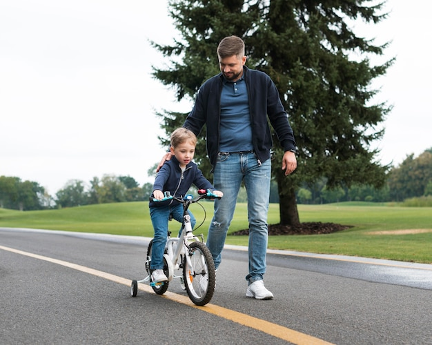 Son riding a bike in the park alongside his father