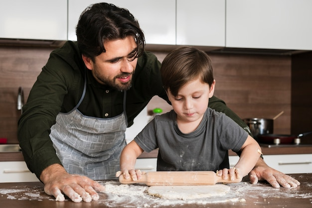 Son rolling dough under father watch