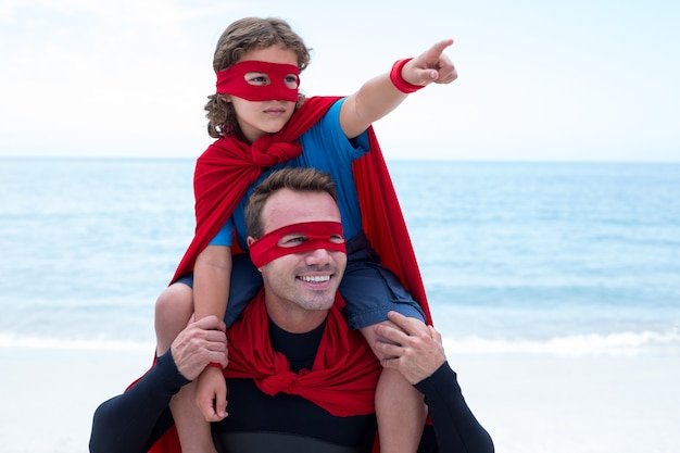 Son in superhero costume pointing while father carrying on shoulder
