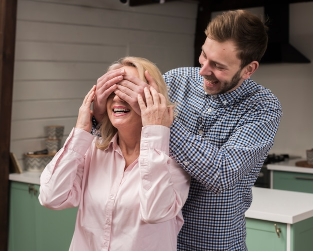 Son surprising mom in the kitchen