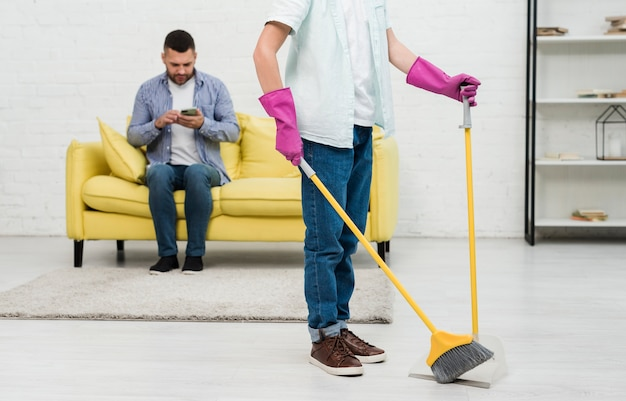 Son using broom while father checks phone