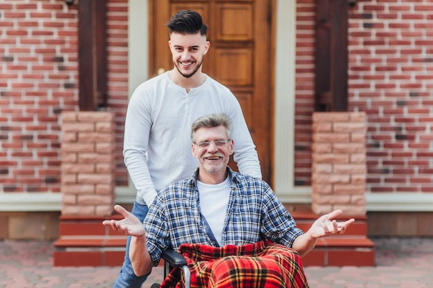 The son walking with his father on wheelchair near nursing home