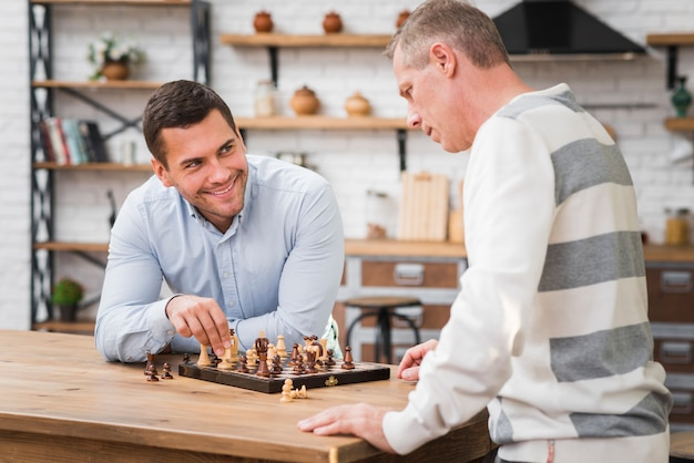 Son winning a chess game in front of his father
