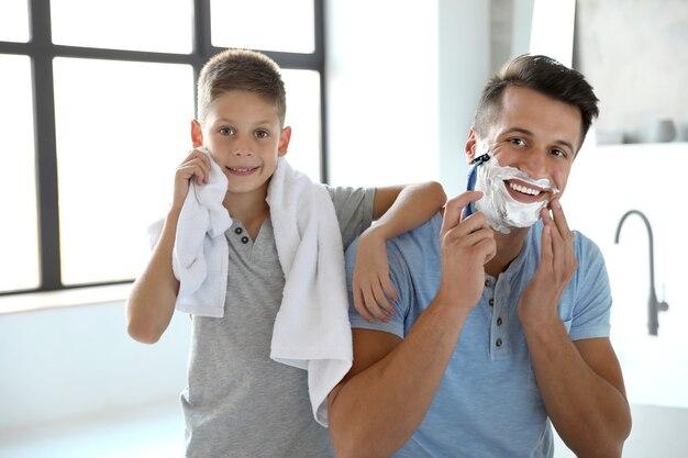 아빠가 화장실에서 면도하는 동안 아들이 수건으로 얼굴을 닦는다