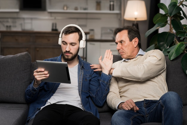 Son with headphones and tablet ignoring father