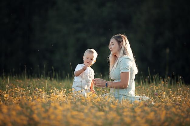 Сын с мамой летом гуляет в поле
