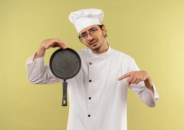 Sonfused giovane cuoco maschio che indossa l'uniforme del cuoco unico e occhiali che tengono e indica la padella sul verde